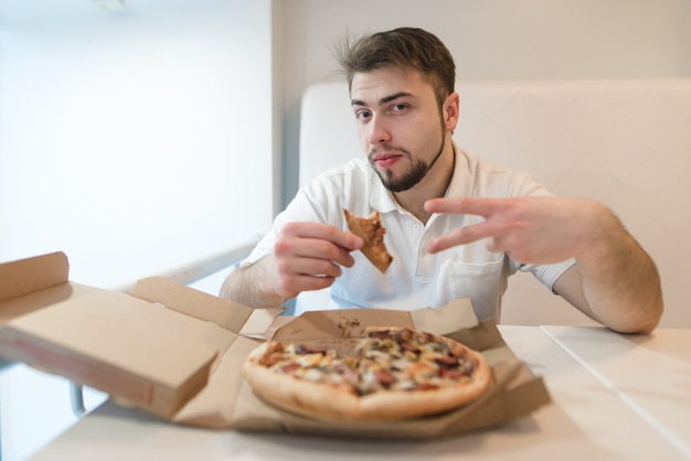 ピザを片手に持っているハンサムな男がカメラにポーズをとります。ピザの箱の近くのテーブルに座っている男