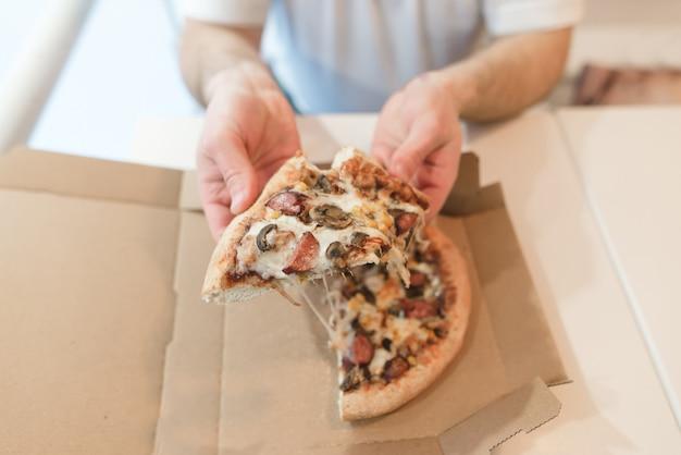男性の手で食欲をそそるピザの断片。男は紙箱から熱いピザを食べます。