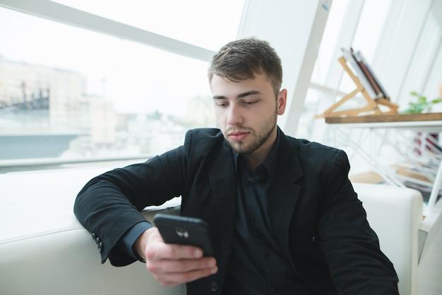 Человек с бородой смотрит на смартфон во время перерыва на обед в кафе. кофе-брейк в стильном светлом кафе.