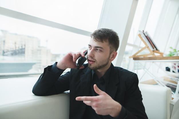 Эмоциональный человек, одетый в черный костюм, сидя в современном кафе и разговаривает по телефону.