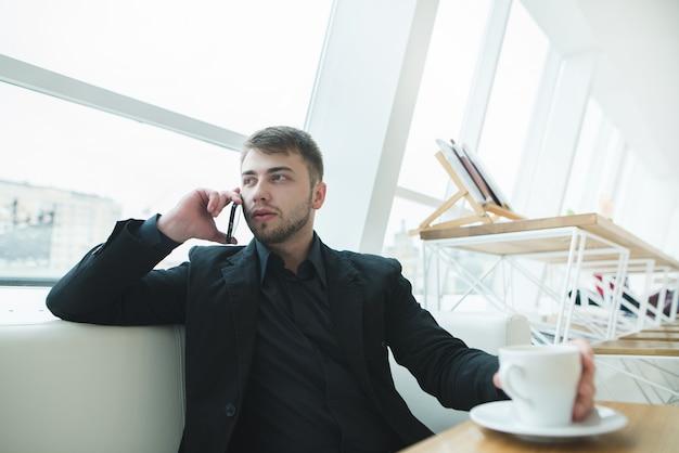 Мужчина сидит у окна у окна в кафе с современным дизайном и говорит по телефону.