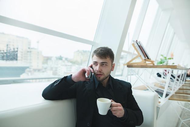 Человек разговаривает по телефону с чашкой горячего напитка в руках. мужчина с бородой сидит в кафе и обедает.