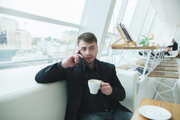Мужчина в костюме сидит за столом в светлом кафе возле окна и разговаривает по телефону.