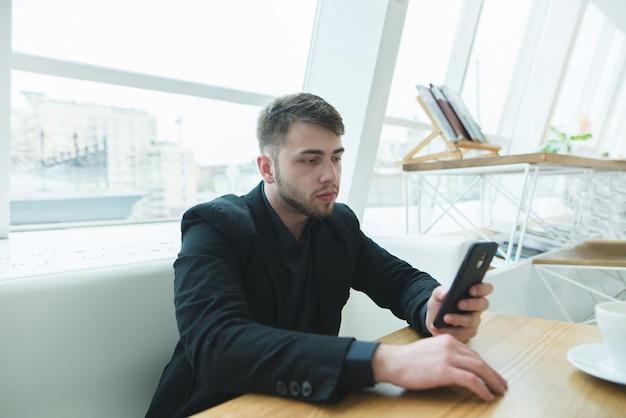 Мужчина в костюме сидит за столом в светлом кафе возле окна и пишет сообщение на своем смартфоне.