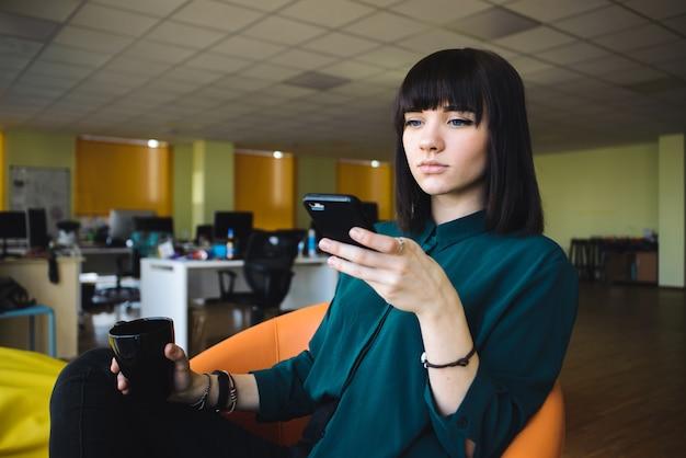 バックグラウンドジョブの近代的なオフィスで若いハンサムなサラリーマン。コーヒーのカップを保持しているビジネスの女性。仕事を休憩。