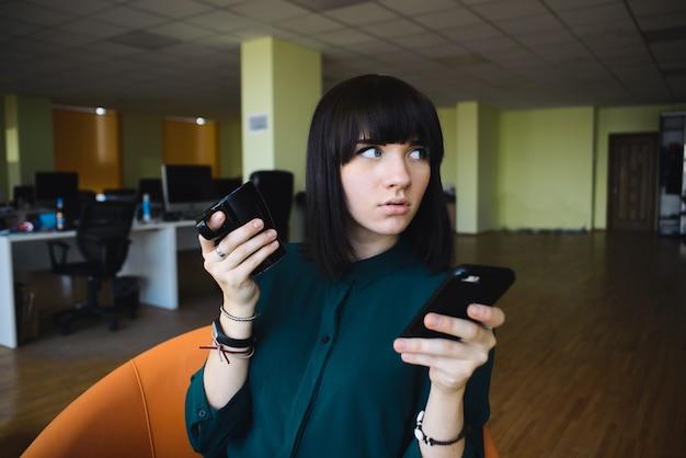 携帯電話を使用してコーヒーを飲む若い、美しいビジネス女性の肖像画。仕事を休憩。近代的なオフィス