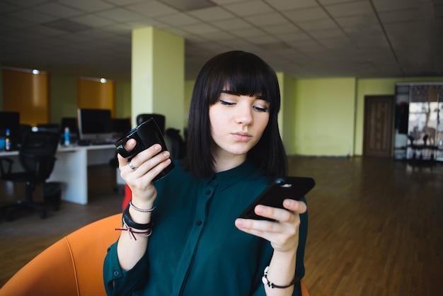 携帯電話を使用して飲み物のカップを保持している若くて美しい女性会社員の肖像画。