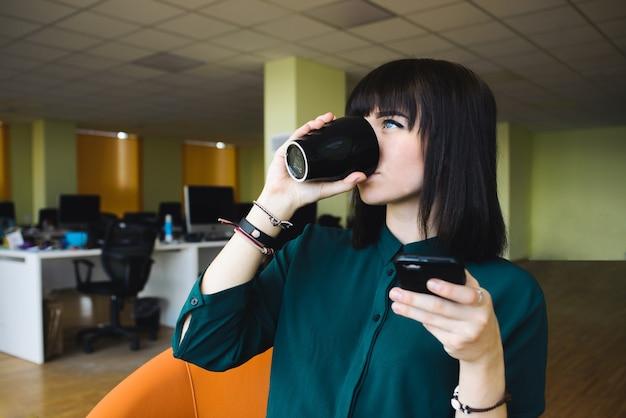 携帯電話を使用して黒いカップからコーヒーを飲む若い、美しい女性会社員の肖像画。