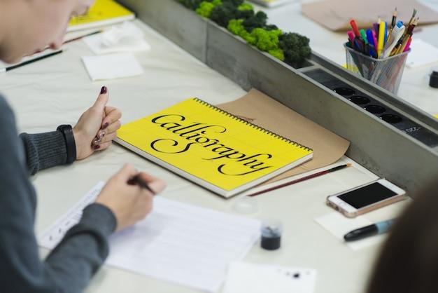 女性は紙にインクでペンを書きます。教育書道