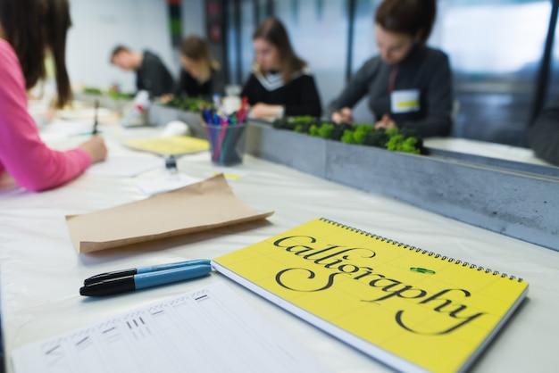 書道を学ぶ学生のグループ。人々は学習の最中です。碑文書道とメモ帳。
