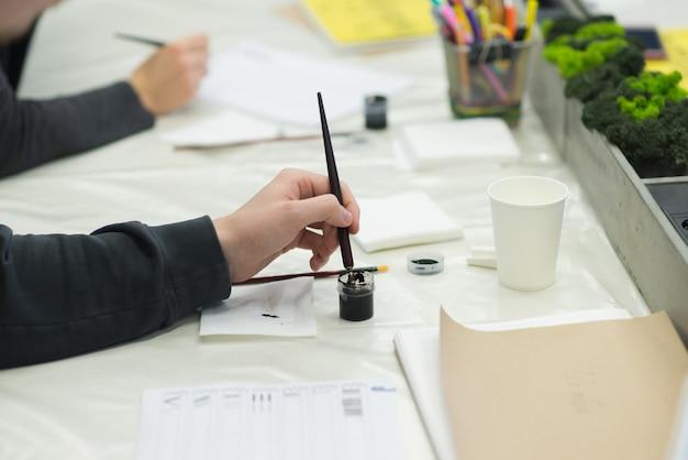 生徒はインクボックスでペンを掘ります。書道を練習します。教育書道