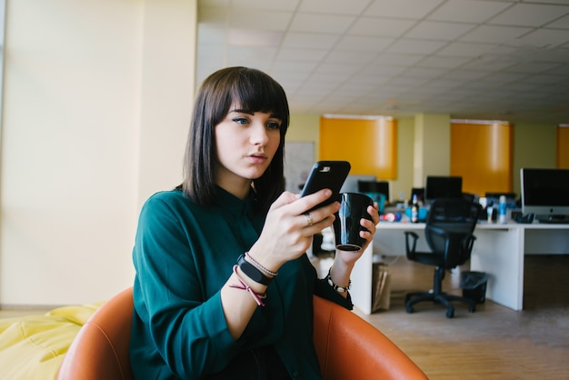 若い、非常に美しいビジネスの女性は、電話と一杯のコーヒーを保持しています。オフィスでの仕事を背景に。