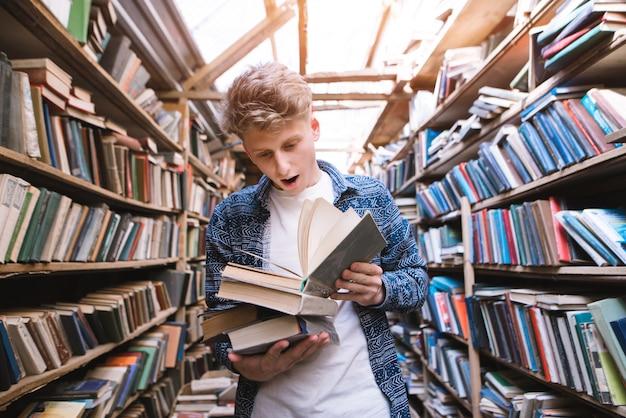 Молодой человек с удивленными эмоциями читает книгу в светлой публичной библиотеке.