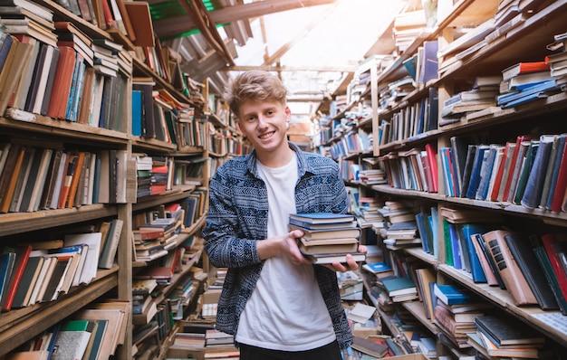 Молодой человек стоит в старой атмосферной библиотеке с книгами в руках