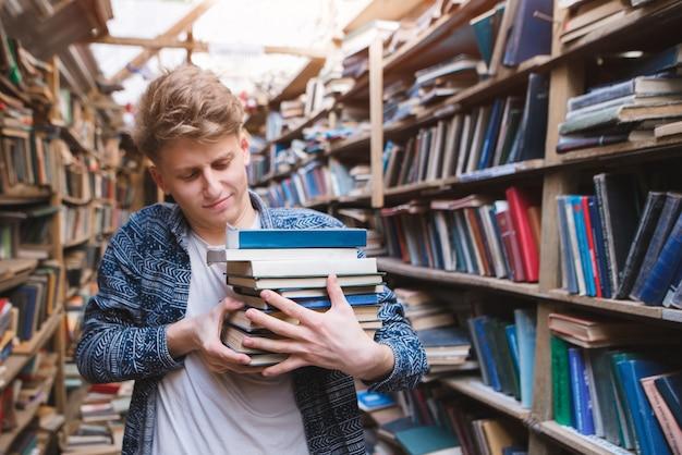 Студент с большим количеством книг в руках старой атмосферной библиотеки.