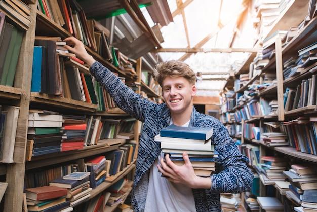 Студент с большим количеством книг в руках находится в библиотеке