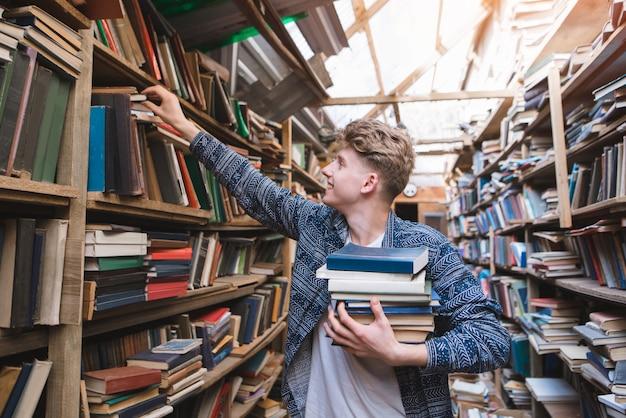 Портрет позитивного студента, который берет книги с книжных полок старой уютной библиотеки