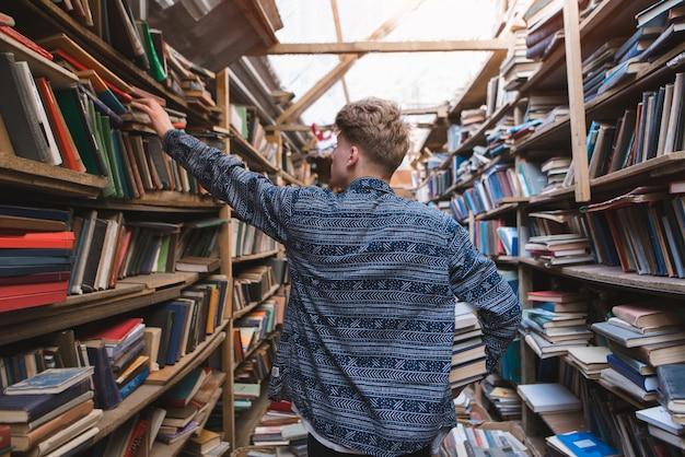 Задняя часть студента, ходить вокруг старой домашней библиотеки в поисках книг.