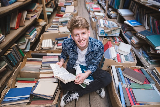 Студент сидит с книгами в руках на полу в публичной библиотеке