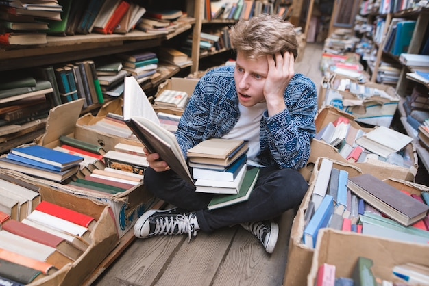 Пораженный молодой человек сидел на полу в публичной библиотеке и читал книгу.