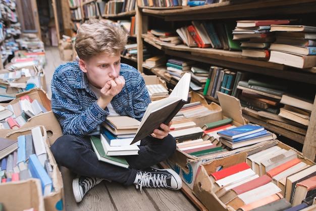 Молодой человек с энтузиазмом читает интересную книгу, сидя на полу в старой библиотеке