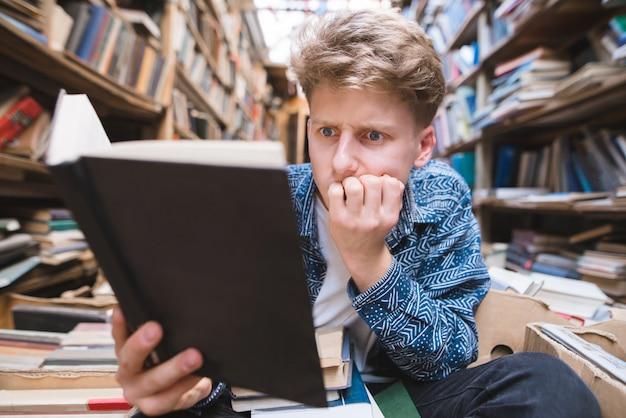 Смешной студент сидит на полу в старой публичной библиотеке и читает книгу с заинтересованным взглядом.