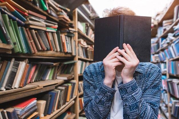 Студент стоит в уютном, старом, публичном бюллетене и держит перед собой книгу.