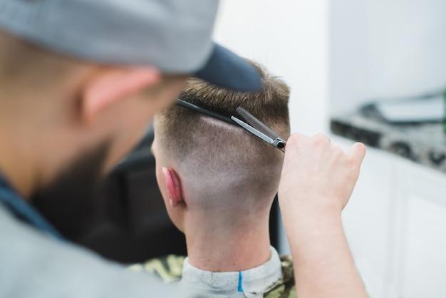 Мужской парикмахер создает стильную прическу для клиента. парикмахерские ножницы ее волосы с молодым человеком.