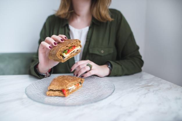 Аппетитный бутерброд в руках молодой девушки. сэндвич в макро и в фокусе.