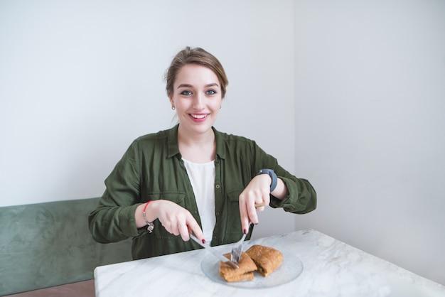 Красивая девушка сидит в ресторане и ест бутерброд с ножом и вилкой. обед в светлом кафе.