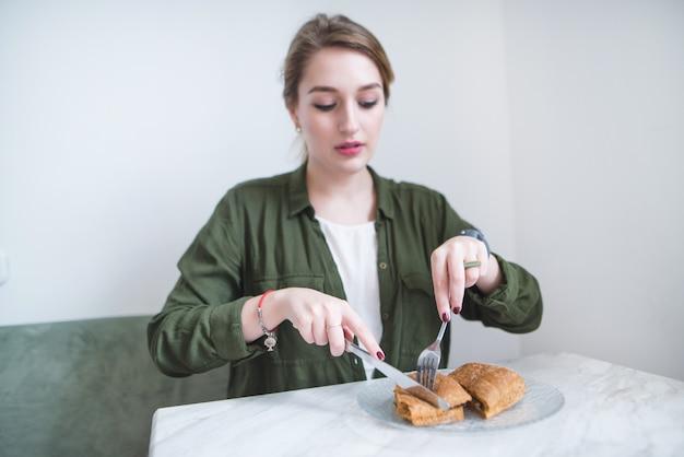 Девушка сидит в светлом ресторане и ест бутерброд с ножом и вилкой. женщина завтракает в кафе