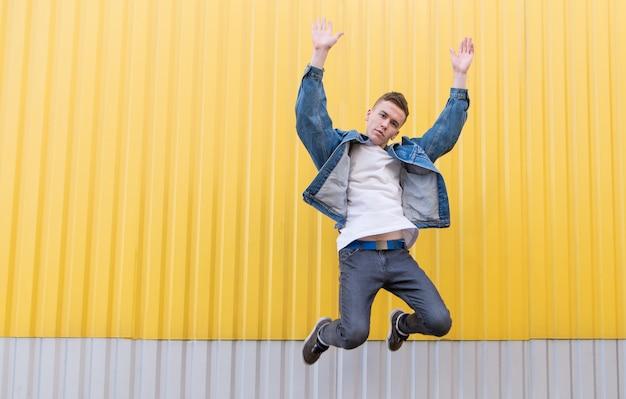 黄色の壁を背景にジャンプしてカメラに探しているスタイリッシュな若者。