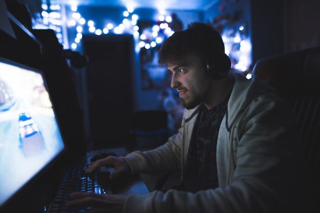 Сконцентрированный молодой человек играет на компьютере в уютной комнате.