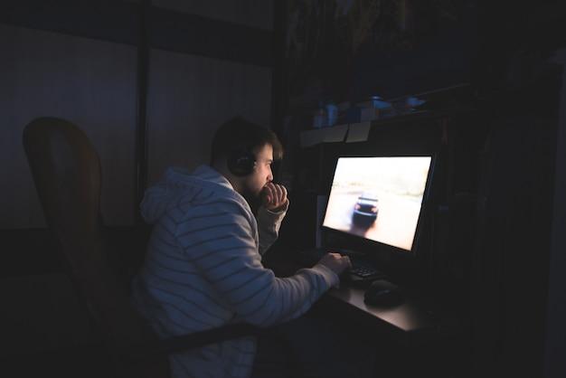 Молодой человек в наушниках садится за компьютер и играет в игру.