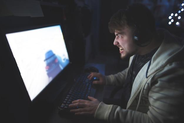 Портрет злого геймера пока играющ дома за компьютером.
