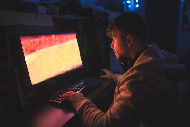 Геймер играет в ужасные игры ночью за компьютером.