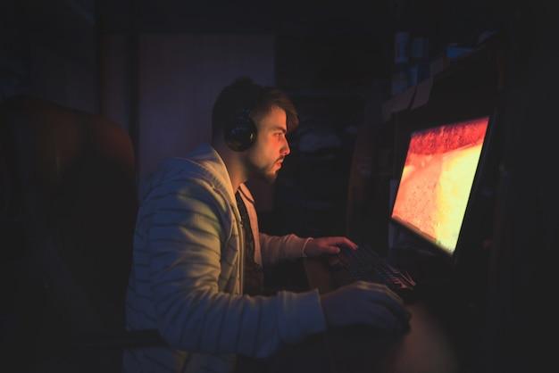 Милый мужчина-геймер сидит в уютной комнате за компьютером и играет в игры.