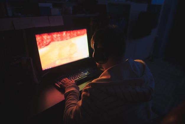 Сосредоточенный геймер сидит за компьютером дома в уютной комнате и играет в ужасные игры