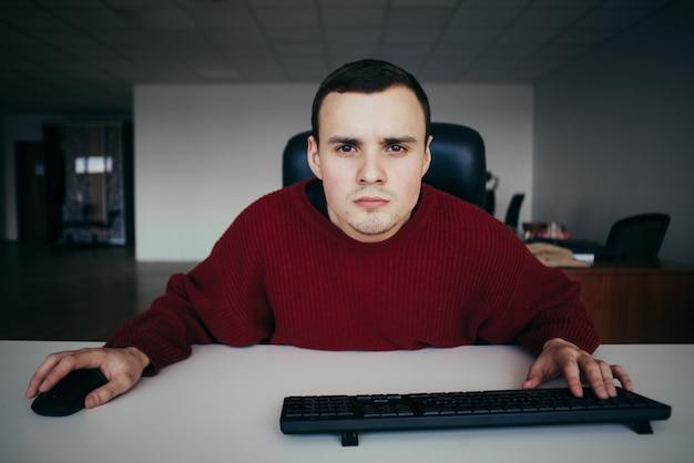 コンピューターのモニターを注意深く見て若い男性会社員。カメラビューに興味がある