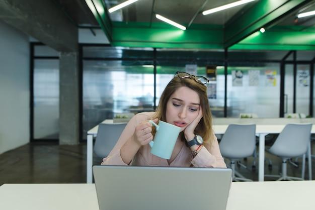 彼女の手にコーヒーのカップを持つ悲しい少女は、オフィスの机の上のラップトップを使用しています。