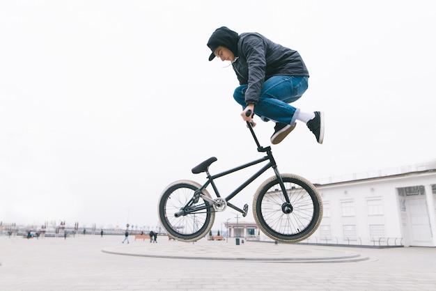 Молодой человек делает эффектные трюки на городской площади.