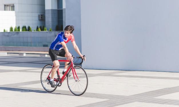 スポーツウェアの男性サイクリストが赤いロードバイクに乗る