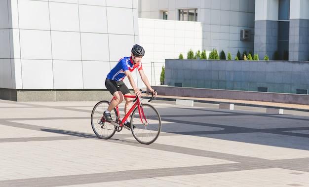 サイクル服の若い男がロードバイクに乗る