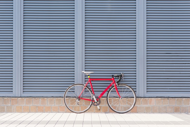 道路の赤い自転車は灰色の壁の上に立つ