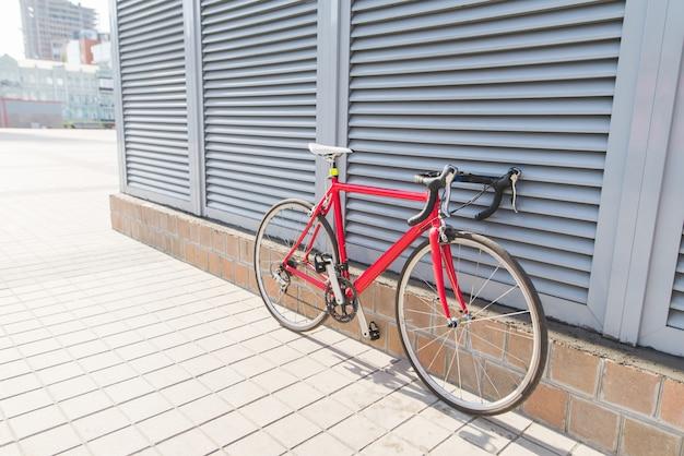 灰色の壁の近くに立つ美しい赤いロードバイク