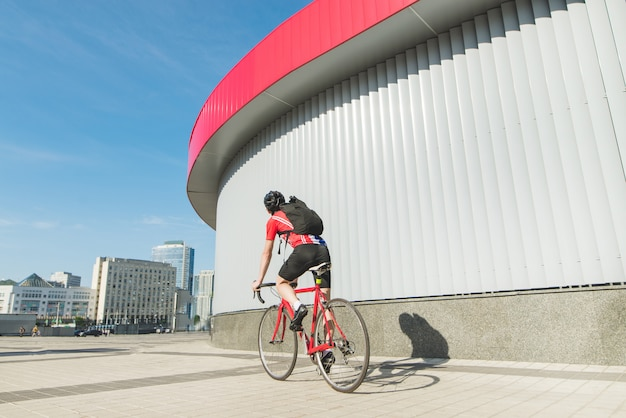 赤いロードバイクに乗るサイクリストの後ろ