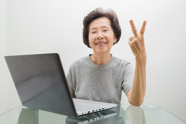 Пожилая дама работает с ноутбуком, работает с ноутбуком