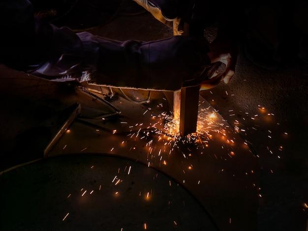 男は暗闇の中で火花で鋼を溶接します。