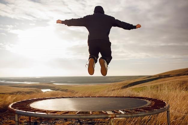 若い男がトランポリンでジャンプ