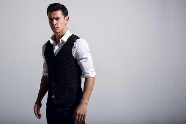 Молодой красавец носить белую рубашку, черный жилет, стоя возле серой стены.